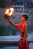 UJJAIN, INDIA - APRIL 23, 2011: Brahmin performing Aarti pooja ceremony at holy river Kshipra. Aarti
