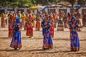 PUSHKAR, INDIA - NOVEMBER 21, 2012: Unidentified Rajasthani girls in traditional outfits dancing at