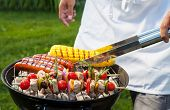 stock photo of bbq party  - Man with tongs cooking on a back yard barbecue - JPG
