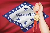 Medal In Hand With Flag On Background - State Of Arkansas. Part Of A Series.