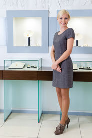stock photo of jewel-case  - Shop assistant stands near the window case at jeweler - JPG