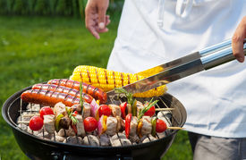 image of tong  - Man with tongs cooking on a back yard barbecue - JPG