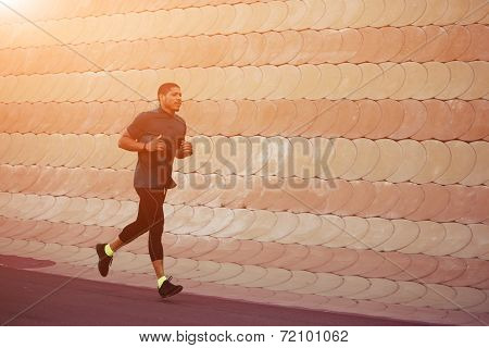 Healthy build sportsman running in the park at soft sunset light