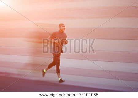 With speed athletic man running at sunset, jogging in the par