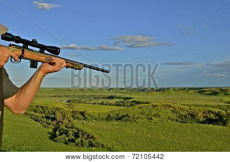 Hunter with rifle takes aim