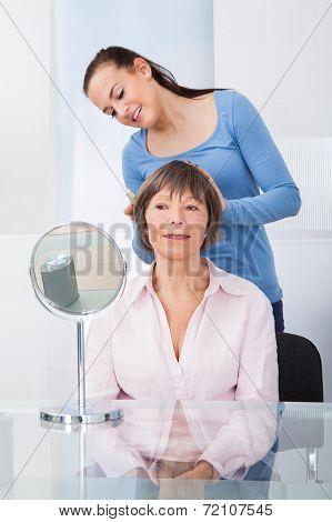 Caretaker Combing Senior Woman's Hair
