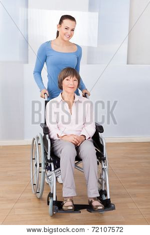 Caregiver With Disabled Senior Woman In Wheelchair