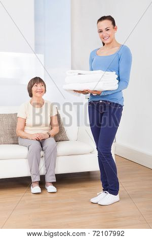Caretaker Carrying Towels With Senior Woman Sitting On Sofa