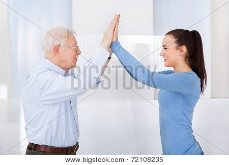 Caregiver And Senior Man Giving High Five