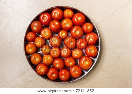 Freshly pluck shiny red tomatoes kept in a plate on an isolated background