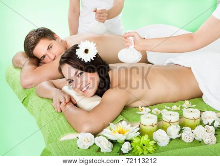 Couple Receiving Massage With Herbal Compress Balls