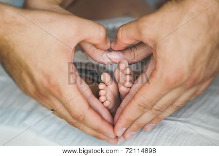 The baby's legs in the hands of MOM and dad