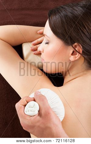 Woman Receiving Herbal Massage With Stamps At Spa