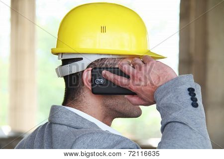 Engineer at a construction site making a business call