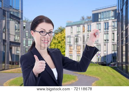 Real Estate Agent With Key Standing On Street Against Modern Building