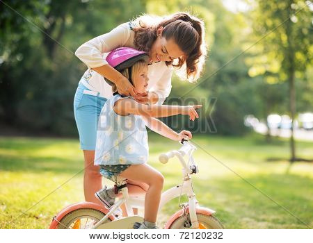 Mother Wearing Helmet On Baby Girl On Bicycle