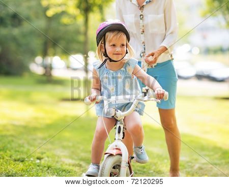 Mother And Baby Girl Riding Bicycle Outdoors