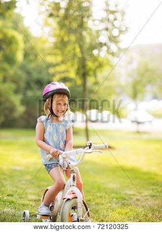 Portrait Of Smiling Baby Girl With Bicycle In Park