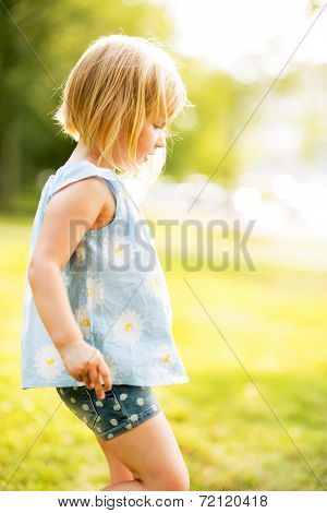 Profile Portrait Of Baby Girl Outdoors In Park