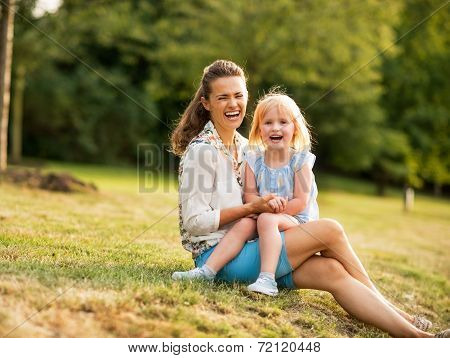 Portrait Of Happy Mother And Baby Girl Sitting Outdoors