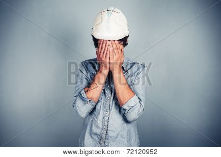 Blue Collar Worker Covering His Face