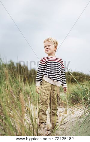 Beautiful kid standing in the dunes and watching something