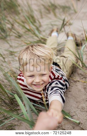 cheerful boy playing on the beach