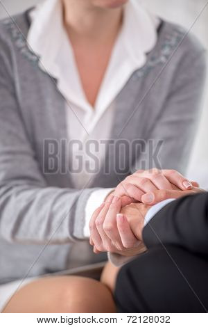 Close-up of psychiatrist keeping her hands together with patient