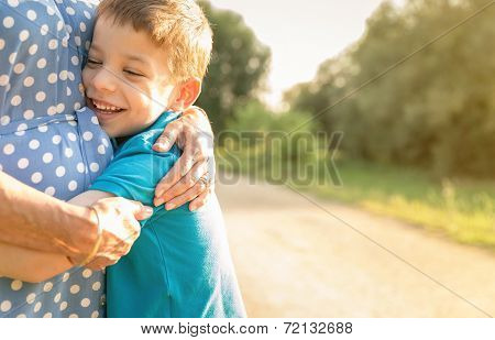 Happy grandson hugging to his grandmother outdoors