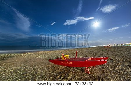 RIMINI, ITALY - JULY 12, 2014: Night sand beach with rescue boat.