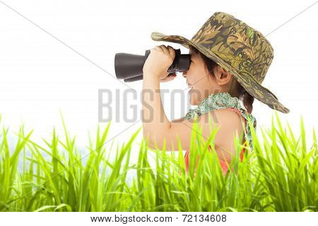 Happy Little Girl holding Binoculars Outdoors.