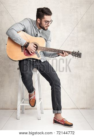 Handsome Man Playing An Acoustic Guitar Against Grunge Wall