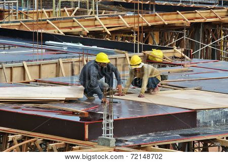 Construction workers fabricating floor slab reinforcement bar and formwork