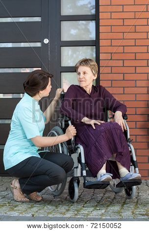 Nurse Talking With Senior Woman On Wheelchair