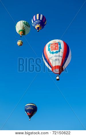 Bright colored balloons fly in blue sky