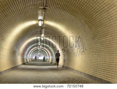 people walking in a long tunnel