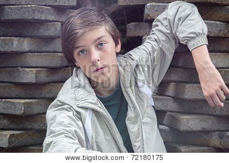Cool Teenager Boy Leaning On A Stack Of Flagstones