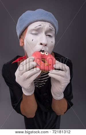 Portrait of handsome male mime eating a tasty pink donut with fu