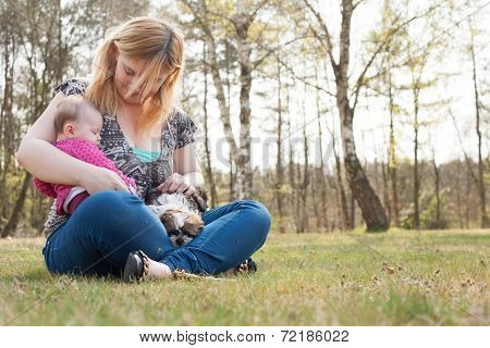 Mother With Puppy And Baby On The Grass