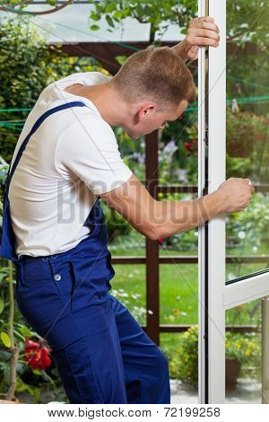 Repairman Adjusting A Window Handle