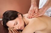 pic of acupressure  - Portrait of beautiful young woman receiving back massaging in spa - JPG