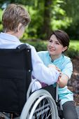 stock photo of wheelchair  - Senior woman on wheelchair with her caregiver outside - JPG