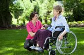 image of wheelchair  - Happy senior woman on wheelchair with caring caregiver outdoors - JPG