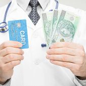 picture of bribery  - Doctor holding money and credit card in his hand  - JPG