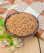 picture of buckwheat  - Buckwheat in a bowl with a flower buckwheat napkin on the background of wooden boards - JPG