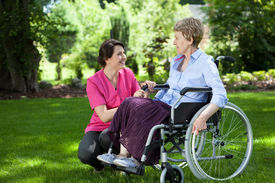 picture of wheelchair  - Happy senior woman on wheelchair with caring caregiver outdoors - JPG