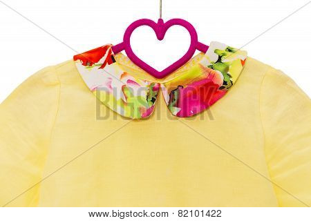 yellow shirt on hanger with floral colar