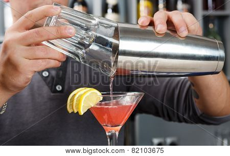 Barman's Hands Mixing Cosmopolitan Cocktail