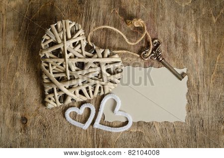 Wicker Heart Handmade With The Key And Two Small Hearts Lying On A Wooden Base With A Sheet Of Paper