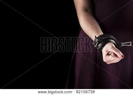 Submissive Woman Wearing A Purple Dress In Leather Handcuffs On Black Background